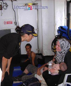 Il comandante Catia Pellegrino a colloquio con una giovane mamma appena tratta in salvo