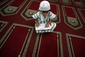 Medio Oriente. La speranza di pace negli occhi delle nuove generazioni. Un bimbo palestinese prega leggendo il Corano (foto Ansa).