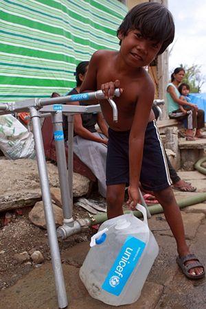 Frederick Amarilla, 8 anni, riempie una tanica di acqua da un rubinetto nella città di Tacloban (Foto Unicef/Maitem)..