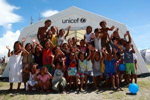 """Alcuni bambini giocano all'estero di una tenda che serve da spazio """"child friendly"""" dell'Unicef nella città di Tanauan (Foto Unicef/Maitem)."""