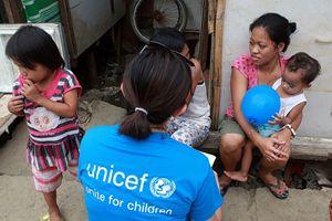 Un'operatrice dell'Unicef parla con una donna e i suoi bambini nella città di Tacloban (Foto Unicef/Maitem).
