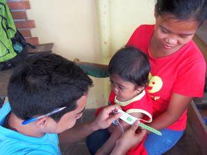 Un operatore Unicef misura la circonferenza del braccio di un bambino filippino per verificarne il livello di crescita e di eventuale denutrizione (Foto UNICEF/Papowitz; l'immagine di copertina è UNICEF/Maitem).)