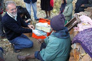il medico Pietro Gamba si prepara a fare una medicazione. In copertina: Gamba con alcuni bambini di Anzaldo, in Bolivia, dove ha fondato e dirige l'ospedale.