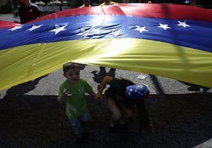 Bambini di Caracas giocano con la bandiera del Venezuela.