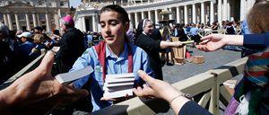 Una giovane volontaria distribuisce ai fedeli in piazza San Pietro il Vangelo tascabile, dono di papa Francesco (Reuters)