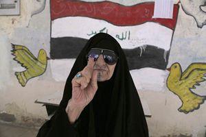 Una donna irachena mostra il dito tinto di viola dopo aver votato (Reuters).