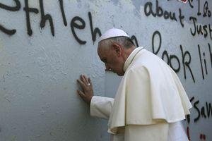 Il Papa in meditazione al muro che divide Israele dai territori palestinesi (Reuters).