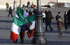 Un venditore ambulante con alcune bandiere dell'Italia (Reuters).