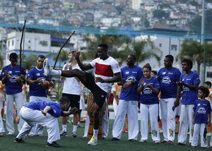 Il calciatore della Nazionale inglese Danny Welback si cimenta nella capoeira durante una visita alla favela Rocinha a Rio (Reuters).