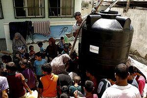 Distribuzione di acqua potabile effettuata da Oxfam (una delle Ong di AGIRE) a Gaza. In copertina: profughi iracheni in fuga (Foto Reuters)