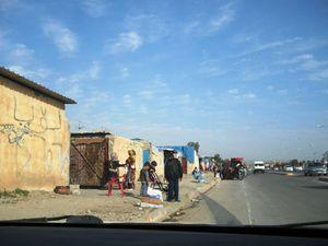 """Gli alloggi dei profughi ai margini della strada definita """"100 metri"""" (Terry Dutto - FOCSIV)."""