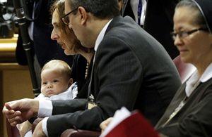 Sopra: Patrizia e Massino Paloni, con il piccolo Davide in braccio, durante i lavori del Sinodo sulla famiglia. Foto Reuters. In alto: i coniugi Paloni in una foto dell'agenzia Ansa.