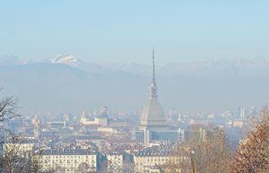 Torino oppressa da una cappa di smog. Foto Ansa. In alto: così Milano, nella zona di Porta Venezia, lunedì 28 dicembre, primo giorno di blocco del traffico. Foto Ansa.