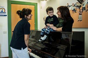 Agostino durante la musicoterapia al pianoforte. In copertina: Agostino e la mamma (le foto sono di Nicolas Tarantino).