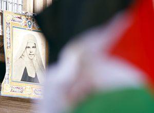 La bandiera della Palestina in piazza San Pietro. sullo sfondo, una delle due sante palestinesi (Reuters).