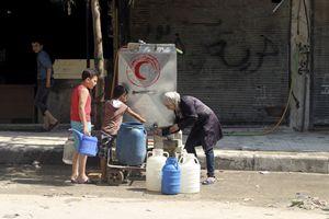 Aleppo, agosto 2015: interrotta l'erogazione costante di gas, luce e acqua l'approvvigionamento idrico s'è fatto difficile. Sopra: un punto di distribuzione di acqua potabile curato dalla Mezzaluna Rossa, l'equivalente della Croce Rossa nel mondo islamico. Foto Reuters.