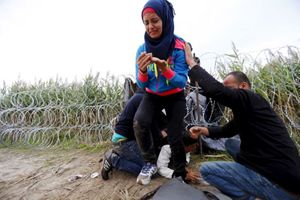 Migranti attraversano la barriera di filo spinato al confine con l'Ungheria (Reuters).