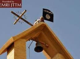 Un militante dell'Isis abbatte la croce su una chiesa di Mosul per issare lo stendardo nero del Califfato.