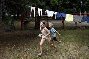Due bambini corrono nel campo di alloggio temporaneo per i rifugiati provenienti dalle regioni orientali dell'Ucraina allestito nella città di Korostyshiv, nella regione di Zhytomyr (foto Reuters)