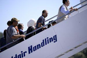 Le famiglie dei profughi mentre salgono sull'aereo papale (foto Reuters)