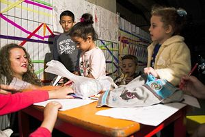 Alcuni bambini profughi giocano al Memoriale della Shoah, alla Stazione Centrale di Milano, che ha aperto loro le porte nell'emergenza.