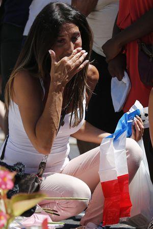 Una ragazza piange mentre deposita fiori e la bandiera per i morti di Nizza.