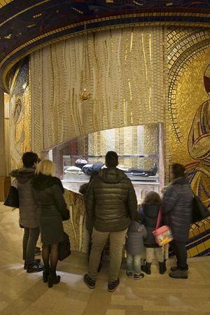 Fedeli in preghiera davanti al Corpo del Santo custodito nel Santuario a lui dedicato a San Giovanni Rotondo (foto Cosmo Laera)