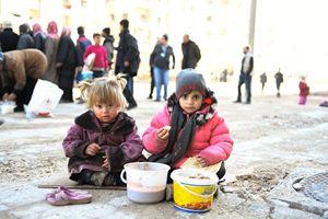 Aleppo, 4 gennaio 2017. Due bambini mangiano qualcosa preparato da una delle Organizzazioni non governative attive nella città martire. Foto Reuters.