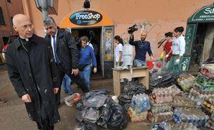 Il cardinale Angelo Bagnasco, arcivescovo di Genova, si reca sui luoghi colpiti dall'alluvione nell'ottobre 2014. Foto Ansa. Le fotografie in alto in copertina sono, invece, dell'agenzia Reuters.