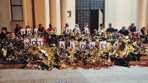 Nella foto: il gruppo di persone che da oltre una settimana dorme col parroco di Lampedusa, don Carmelo La Magra, sul sagrato della Chiesa. La Magra ha detto che continuerà a farlo finché i 42 migranti non saranno sbarcati.