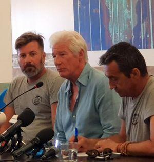 Richard Gere durante una conferenza stampa a Lampedusa, 10 agosto 2019, accanto a lui Riccardo Gatti e un altro dei dirigenti di Proactiva Open Arms.