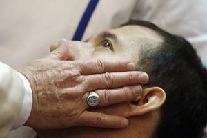 La carezza di papa Francesco a un disabile (Reuters)