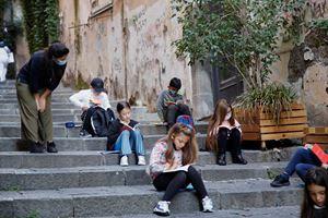 Alunni di Napoli che fanno lezione per la strada, distanziati, dopo la chiusura delle scuole in Campania (foto Reuters).