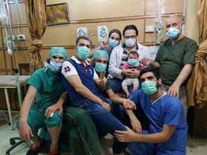 I medici che hanno resistito fino all'ultimo all'ospedale di Aleppo. Al centro, con il camice bianco, c'è Hamza, il marito della regista Waad al Kateab, medico e paladino della rivolta e della resistenza, con in braccio la figlia Sama.