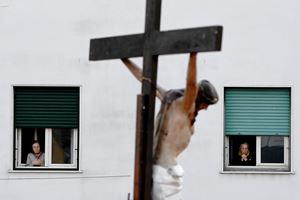 Gli abitanti del quartiere Arenella di Napoli seguono la Via Crucis celebrata dal parroco sul tetto della parrocchia (Ansa)