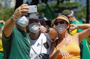 Brasiliani con le mascherine radunati in una manifestazione pro-Bolsonaro il 15 marzo (foto Reuters).