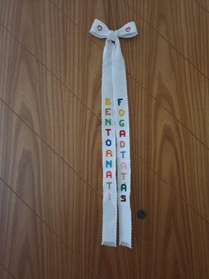 """Il fiocco trovato sulla porta di casa con la scritta """"bentornati"""" in italiano e ungherese."""