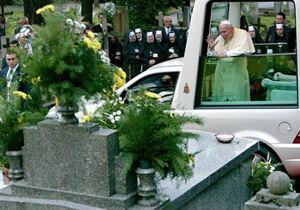 Un papa Giovanni Paolo II stanco ed emozionato davanti alle tombe dei genitori, nel cimitero di Cracovia, il 18 agosto 2002. Foto Reuters.