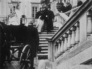 Il re Umberto I di Savoia e la regina Margherita di Savoia, mentre scendono la scalinata d'ingresso della Villa Reale a Monza, nel 1896. Da Wikipedia.