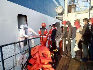 Un gruppo di migranti va a bordo della Moby Zaza per la quarantena.