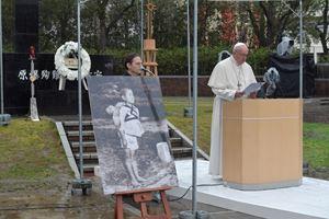 Papa Francesco a Nagasaki (con accanto la foto del bambino che aspetta il suo turno al forno crematorio con il fratellino morto sulle spalle) il 24 novembre 2019. Foto Reuters.