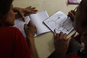Un incontro di catechismo in una parrocchia a Caloocan, al nord di Manila, nelle Filippine. Foto Ansa. In alto: strumenti di catechesi. Foto Ansa.