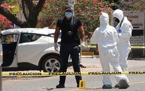Poliziotti e medici legali lavorano sul luogo dov'è stata uccisa Ivonne Gallegos, candidata sindaco a Ocotlan de Morelos, nello Stato di Oaxaca, in Messico, il 20 marzo 2021. Foto Ansa.